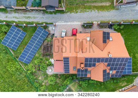 Aerial top view of new modern residential house cottage with blue shiny solar photo voltaic panels system on roof. Renewable ecological green energy production concept. stock photo