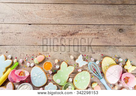 Easter cooking baking background with pastel colored easter cookies, sugar sprinkles and ingredients for bake cake and cookies.  Wooden rustic background, flatlay banner copy space stock photo