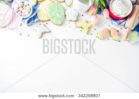 Sweet Easter baking cooking background with traditional Easter bunny and egg cookies, sugar sprinkles, ingredients, utensils. White table background copy space layout stock photo