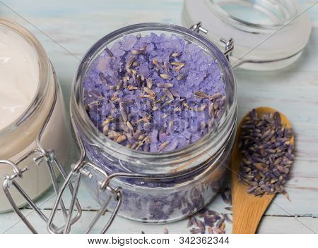 Facial cream and lavender and almond bath salt, on a light wooden background. Cosmetics and natural medicine stock photo