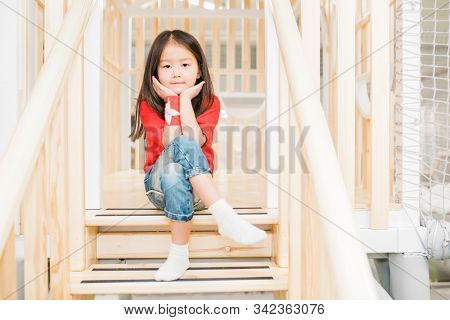 Adorable Asian girl in casualwear sitting on wooden stairs at play area between railings and looking at you stock photo