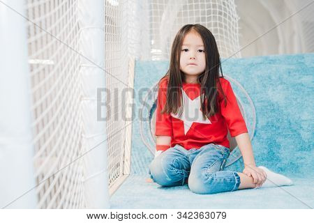 Pretty little Asian girl with long hair wearing costume of super girl looking at you on play area stock photo