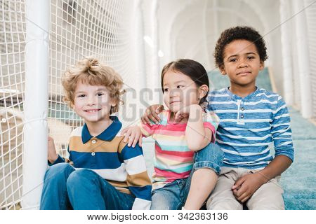 Adorable and affectionate intercultural boys and girl in casualwear gathered together on play area at leisure center stock photo