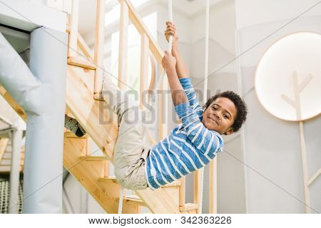 Happy little cute boy of African ethnicity holding by rope while hanging over wooden staircase during play stock photo