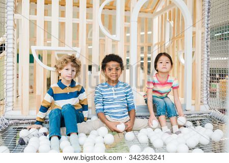 Three cute children of various ethnicities playing with white balloons on playground at leisure center stock photo
