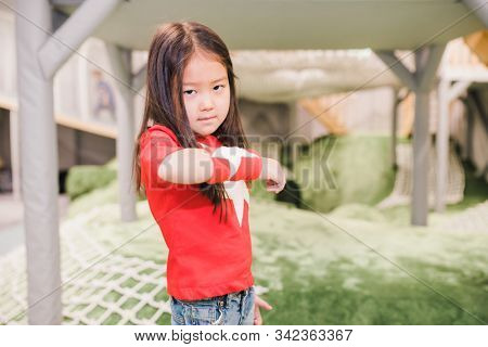 Adorable little girl of Asian ethnicity wearing red t-shirt and handband with white stars playing in kindergarten stock photo