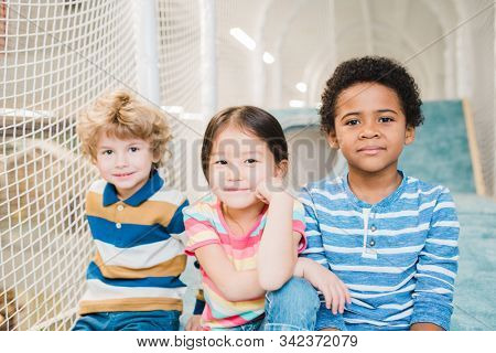 Cute restful boys and girl of Asian, Caucasian and African ethnicities spending time on play area at leisure center stock photo