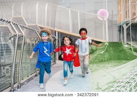 Cheerful cute little kids of Asian, African and Caucasian ethnicities holding by hands while running along playground stock photo