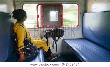 Woman listening music on mobile phone and looking outside from window while traveling solo in train. Traveler enjoying Modern technology on the move in everyday life and travel. Side view Close up portrait - Young Adult Lady - Indian ethnicity. stock photo