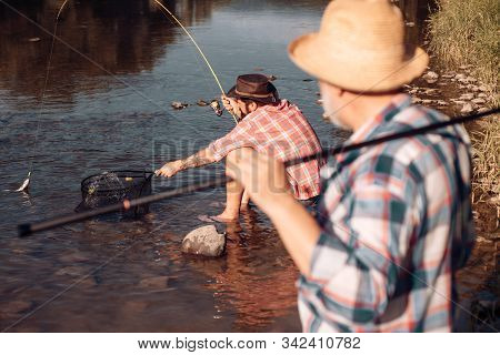 Bearded men catching fish. lear water river. Hobby sport activity. Elegant bearded man and brutal hipster fishing. Guy fly fishing. Nice day for fishing. Retirement is just the beginning stock photo