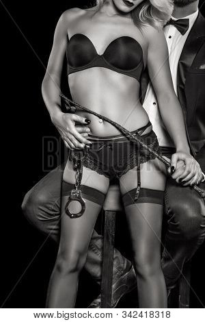 Rich man holding dominant woman with whip and handcuffs and underwear body closeup, bdsm, isolated, black and white stock photo