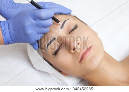 Permanent make-up for eyebrows of beautiful woman with thick brows in beauty salon. Closeup beautician doing  tattooing eyebrow. Face close-up. Make-up concept stock photo