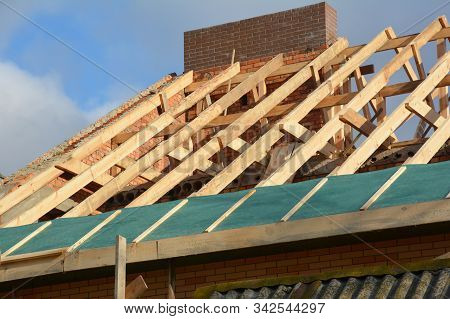 House rooftop wooden frame construction. Incomplete house rooftop roofing construction trusses, vapor barrier,  wooden beams, eaves, timber. stock photo