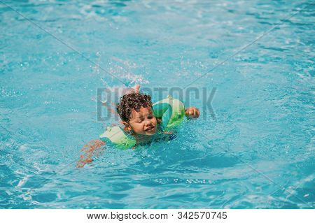 Cute african toddler boy swimming in pool with inflatable arm rings stock photo