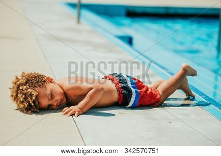Very tired toddler boy lying down by the pool stock photo