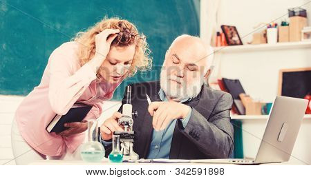 Teacher and girl with notepad near chalkboard. Biology science. Study biology. College university education. Biologist or chemist with microscope teaching student biology. Biological research stock photo