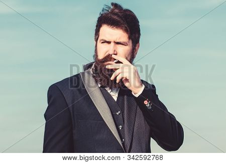 Truth about smoking pleasure and nicotine addiction. Guy with cigarette enjoy nicotine influence. Man with beard and mustache hold cigarette. Bearded hipster smoking cigarette blue sky background stock photo