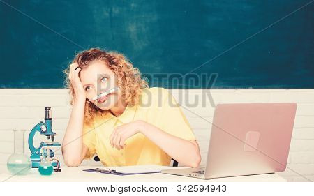 Stressful student life. Stressful day. Teacher stressful occupation. Girl emotional with laptop and microscope working on own investigation biology and chemistry. Mental health and stress influence stock photo