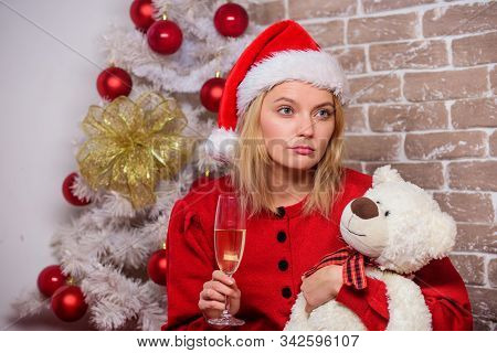 Lonely woman with teddy bear toy and champagne glass christmas eve. Nostalgic moments. Melancholy emotions. Merry christmas and new year. Dreamy mood. New year is coming. Christmas eve. Alone at home stock photo