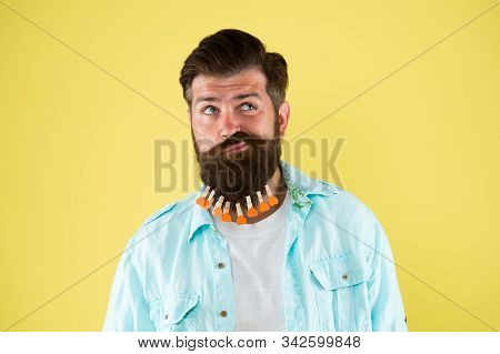 how do i look. valentines day. hair drying in hairdresser. individual hairstyle for male. man clothespin on beard. brutal hipster with clothespin hearts. bearded man casual style yellow background. stock photo