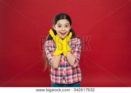 Happy housekeeper. Little housekeeper wear rubber gloves red background. Small girl housekeeper. Housekeeper or domestic worker. Household maid. Home cleaner. Cute housegirl. Domestic assistant. stock photo