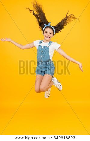 full of energy. Active girl feel freedom. Fun and relax. feeling free. carefree kid on summer holiday. time for fun. retro beauty in mid air. Jump of happiness. small girl jump yellow background. stock photo