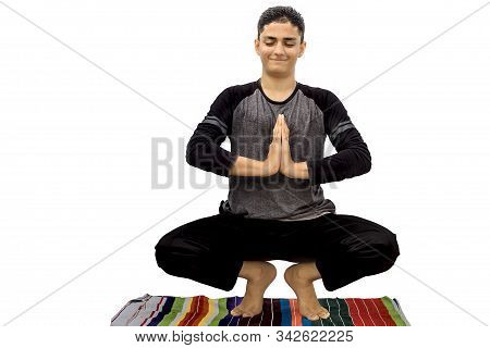 Full-length shot of male teenager doing Malsasana yoga pose isolated. Isolated shot of male teenager doing Mālāsana Yoga pose with slight variation with it on a colorful mat. Male Garland Yoga pose. stock photo