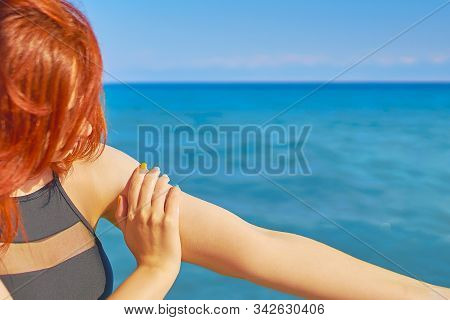 Woman applying sun protection lotion. Tanned woman body applying sun uv protection cream. stock photo
