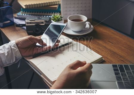 On 2020 Calendar book,Female'hand of planner writing daily appointment.Woman mark and noted schedule(holiday trip) on diary at office desk.Calendar reminder event for planner concept stock photo