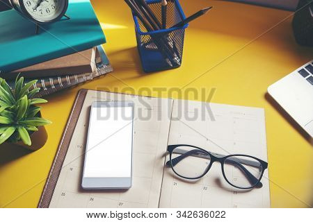 Diary,Calendar and agenda for Planner to plan timetable,appointment,organization,management on table.Desktop Calender 2020 and smart phone place on wooden office desk.Calendar Background Concept. stock photo