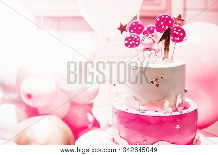 Pink cake with pink balloons for birthday  on pink background. The first day of birth. The girl or boy of 1 year. Interior. Pink balloons. Soft focus. stock photo