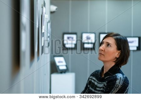 Side view of young Caucasian woman standing in an art gallery in front of black and white framed photos displayed on a gray wall. stock photo