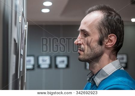 Side view of Caucasian man standing in an art gallery in front of black and white framed photos displayed on a gray wall. stock photo