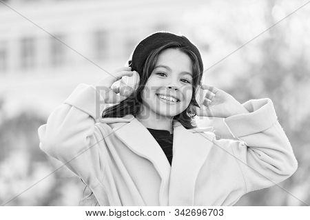 Girl with headphones urban background. Skip track. Favorite band. Influence of music. Child girl autumn outfit enjoying music. Teenage music taste. Little girl listening music enjoy favorite song. stock photo