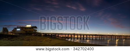 What used to be the longest wooden pier in California still holds beauty at dawn with Made West and Beach House signs lighting the facade in Ventura, California, USA on New Year's morning, 2020. stock photo