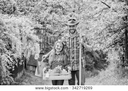 Family dad and daughter little girl planting plants. Day at farm. Popular in garden care. Planting flowers. Plant veggies. Planting season. Inspect your garden daily to spot insect trouble early stock photo