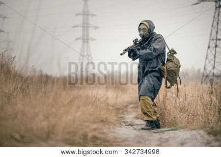Soldier with airsoft rifle in raincoat and gas mask outdoor. stock photo