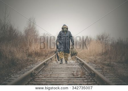 Soldier in gas mask and raincoat with a rifle walking on the empty railroad concept. stock photo