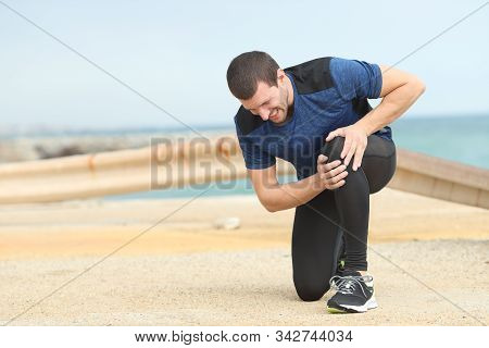 Painful runner complaining suffering knee ache after sport on the beach stock photo