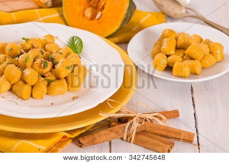 Pumpkin gnocchi with grated amaretti cookies on white dish. stock photo