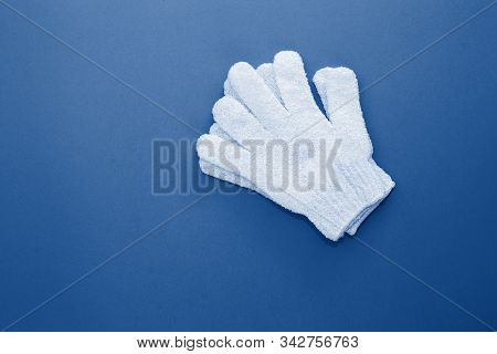 Woman exfoliating massage glove on blue background.Gloves for use in shower for massage and scrub. Beauty background with cosmetic products toned trendy classic blue color of the year 2020. stock photo