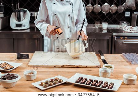 Cropped View Of Chocolatier Holding Cooking Thermometer Near Bowl With Melted White Chocolate