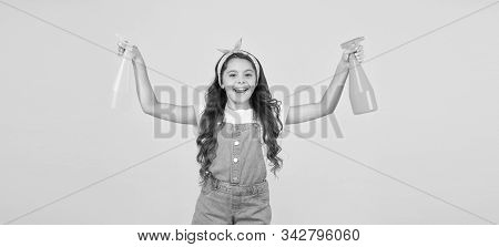 Miss clean. Clean home is happy home. Happy little girl hold spray bottles on yellow background. Small child keep house clean. Cleaning dirt. Household work. All surfaces clean at all times. stock photo