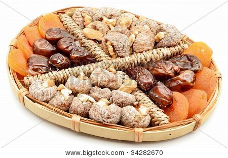 Figs, apricots, dates and walnuts on a tray surrounded by white background stock photo