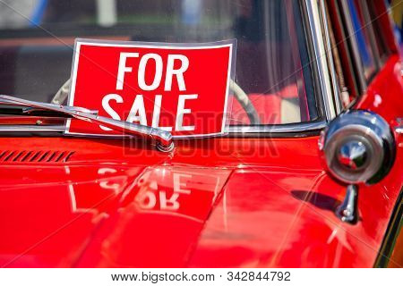 FOR SALE, red sign on classic antique American bright red car hood and chrome parts close up, during outdoor old cars show stock photo