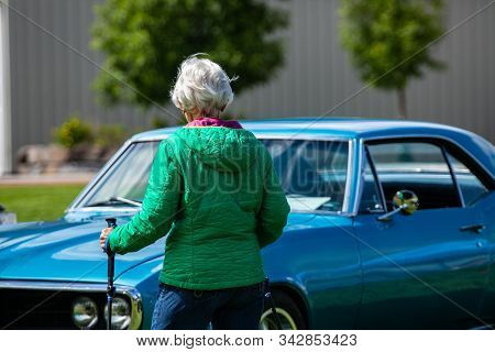 rear view of an old woman walking with hiking crutches, in front of classic muscle American blue car with opened hood during outdoor antique car show stock photo