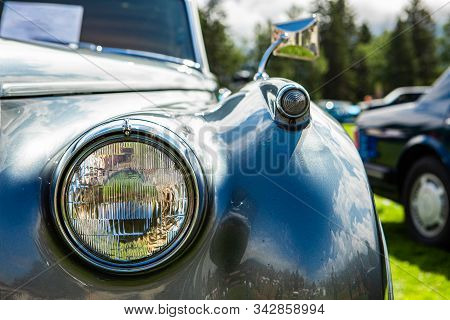 bright metal grey old classic antique American car front part, right side, close up glass headlight with chrome frame, blurred cars outdoor background stock photo
