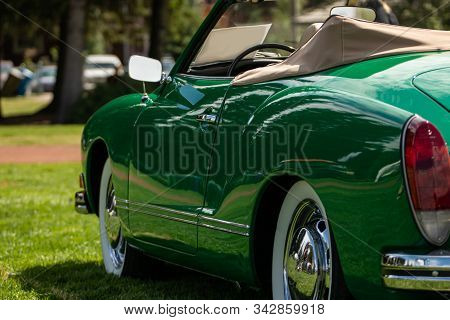 classic antique American green Convertible car side view from the back selective focus, with open roof and chrome wheels, during outdoor old cars show stock photo