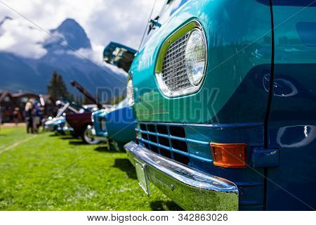 Old Vintage Classic American turquoise blue van car, chrome bumper front close up, on the grass during an outdoor show, people and cars background stock photo