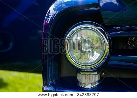 Bright blue old classic antique American car half front, left side, close up on glass headlights and signals light lamps stock photo